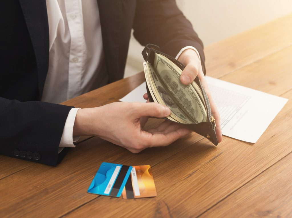 Man's hands holding open wallet with money
