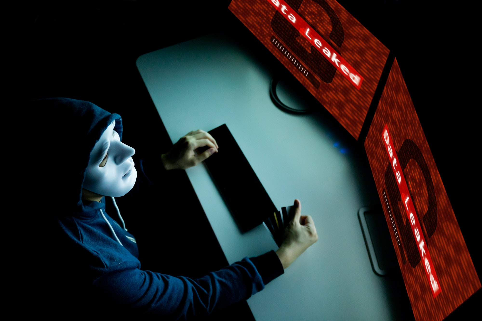 Masked hacker under hood using computer to hack into system and employ data leaking process