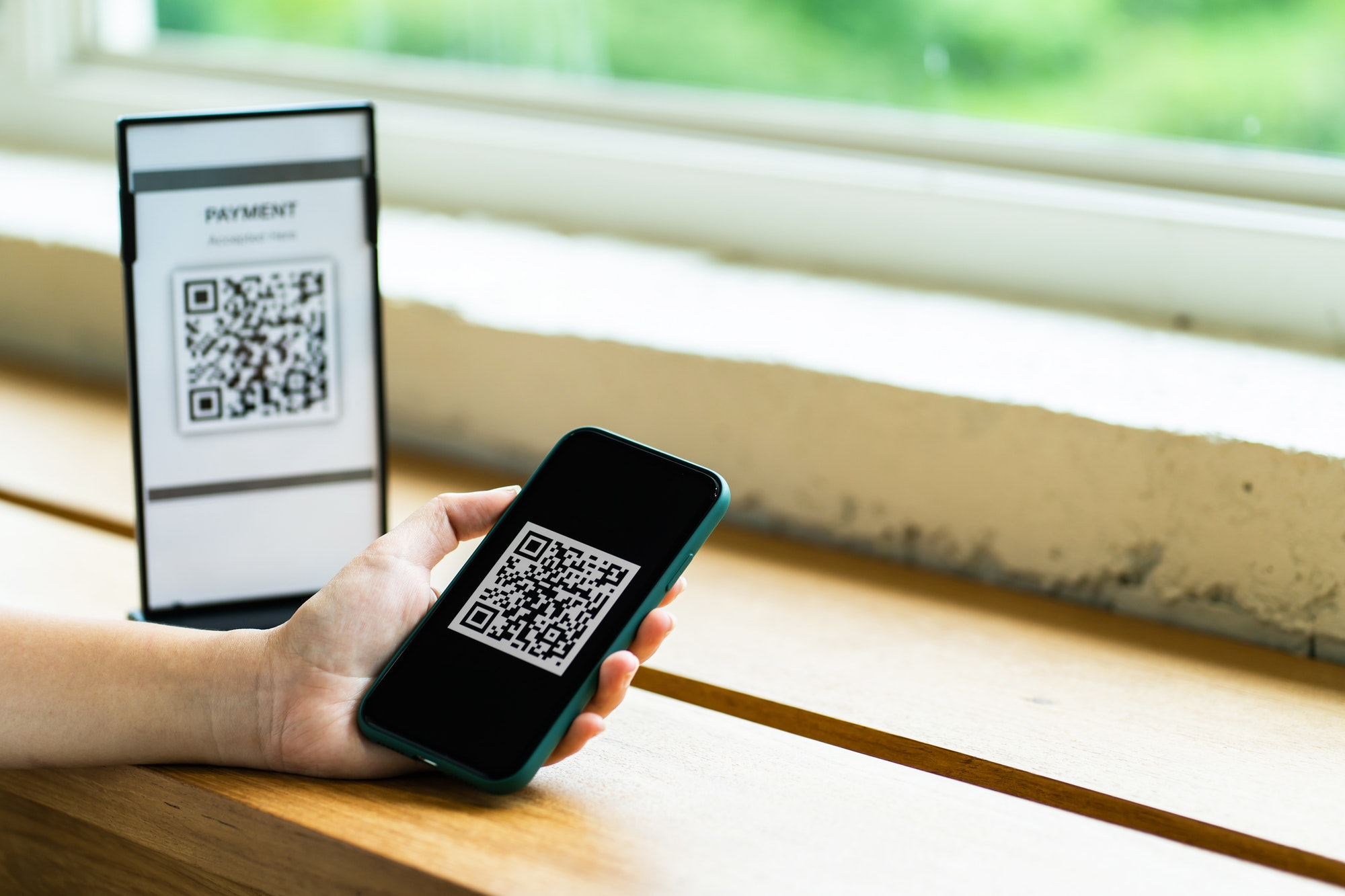 Online money, Close up hand holding smart phone for scanning Qr code for digital payment.